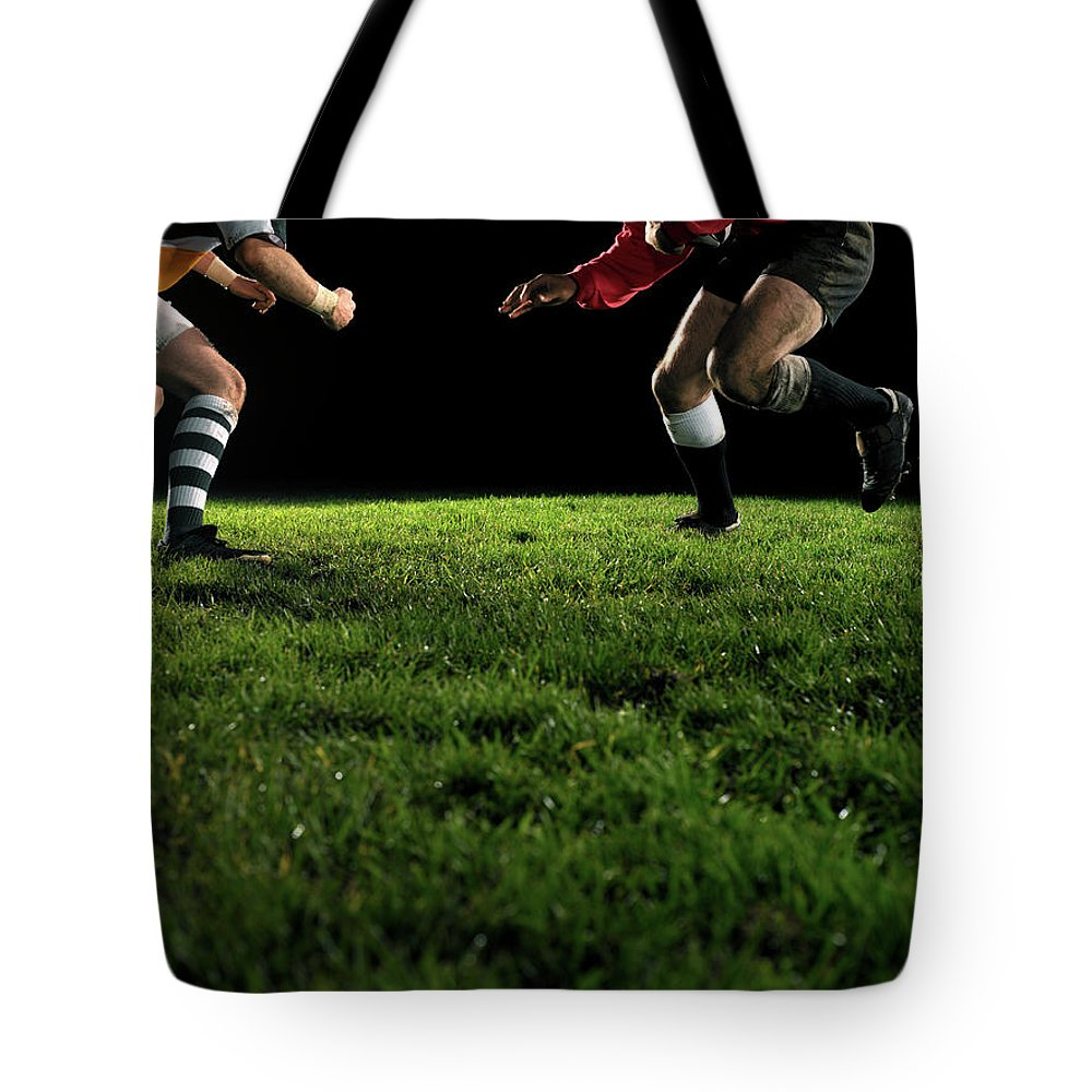 Grass Tote Bag featuring the photograph Two Opposing Rugby Players, One Holding by Thomas Barwick