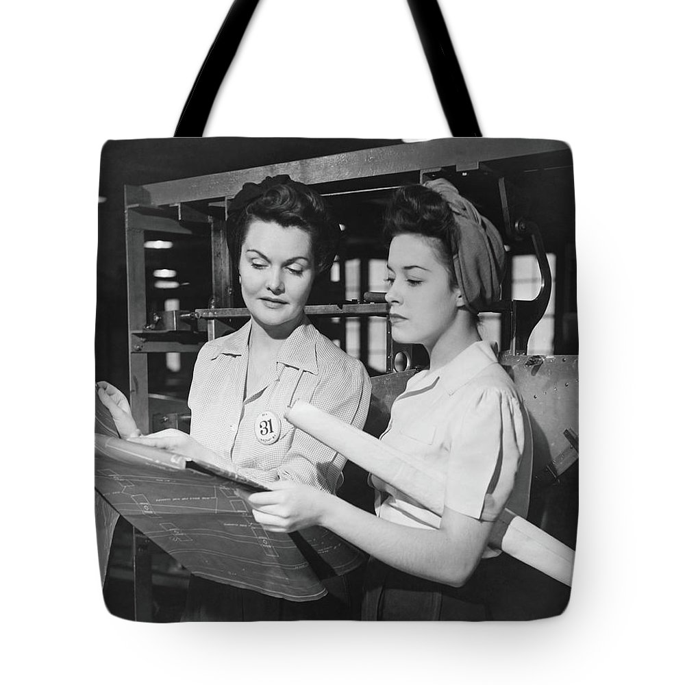 Plan Tote Bag featuring the photograph Two Women In Workshop Looking At by George Marks
