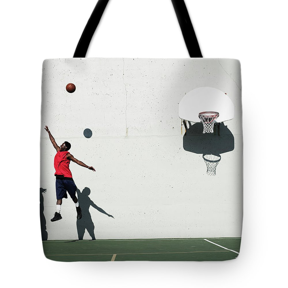 Young Men Tote Bag featuring the photograph Two Young Men Playing Basketball by Thomas Barwick