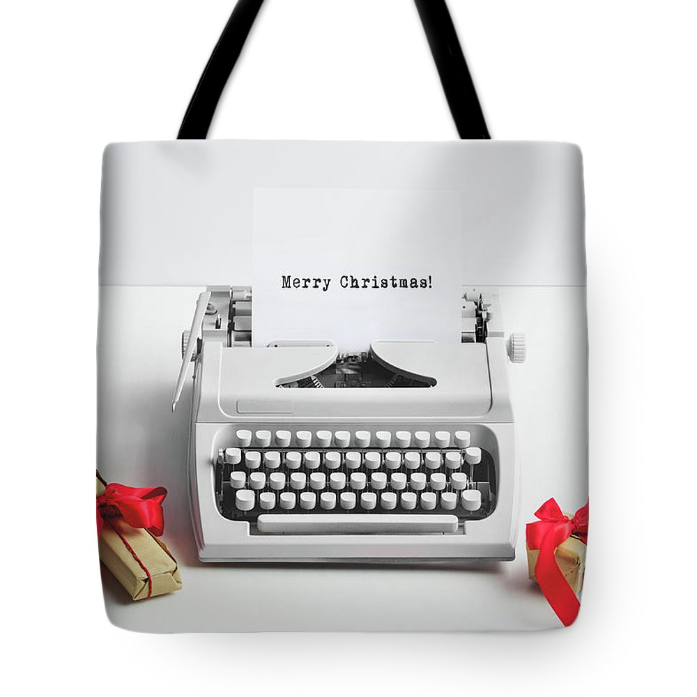 Christmas Tote Bag featuring the photograph Typewriter With Merry Christmas Text And Gifts by Michal Bednarek