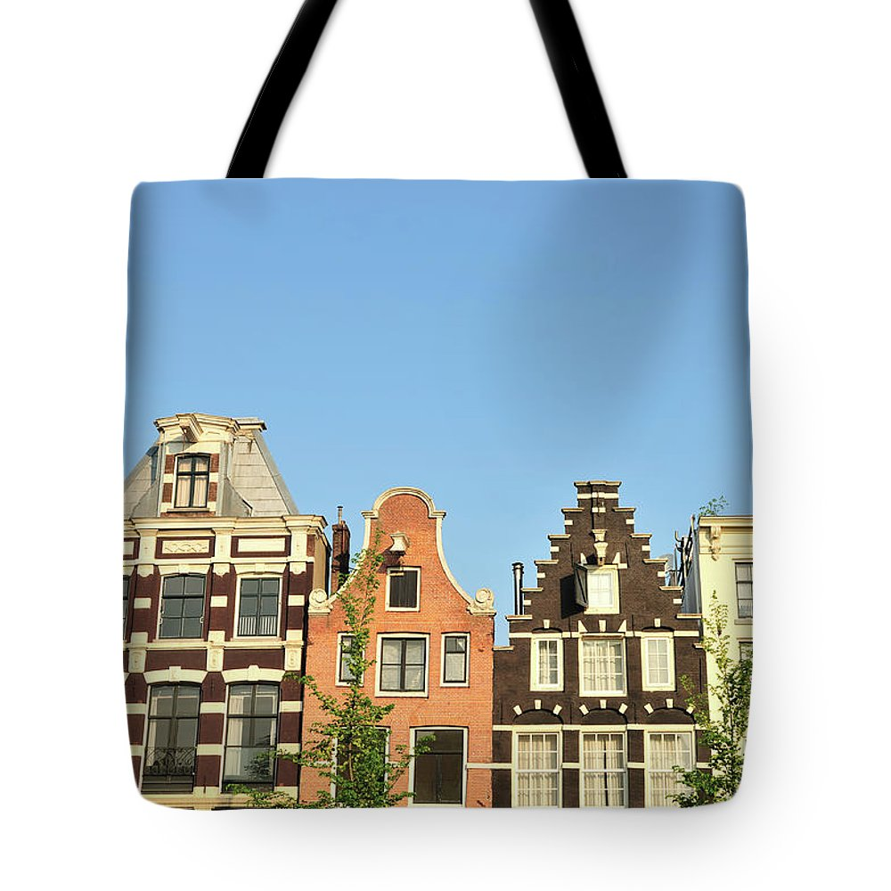 In A Row Tote Bag featuring the photograph Typical Canal Houses, Amsterdam, The by Gorazdbertalanic