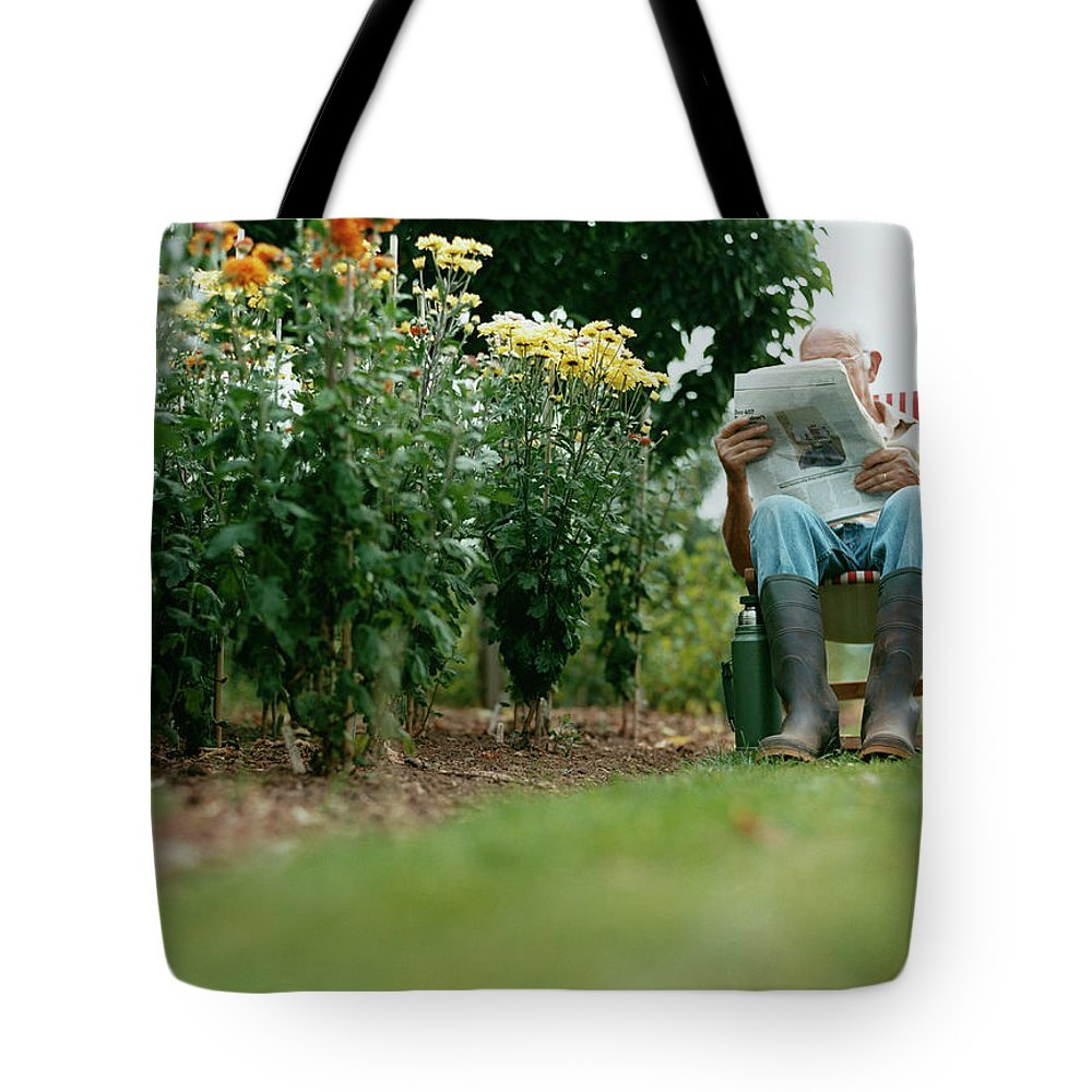 Grass Tote Bag featuring the photograph Unrecognisable Man Sits Reading A by Iain Crockart