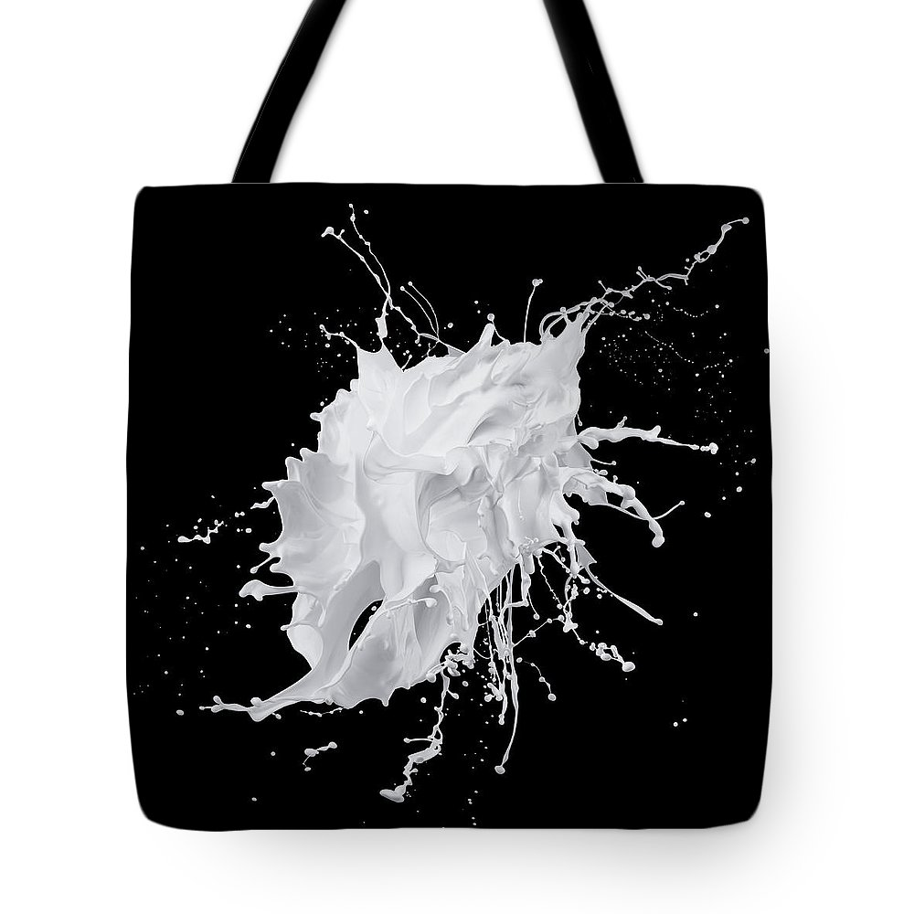 Black Background Tote Bag featuring the photograph White Paint Splash On Black Background by Biwa Studio