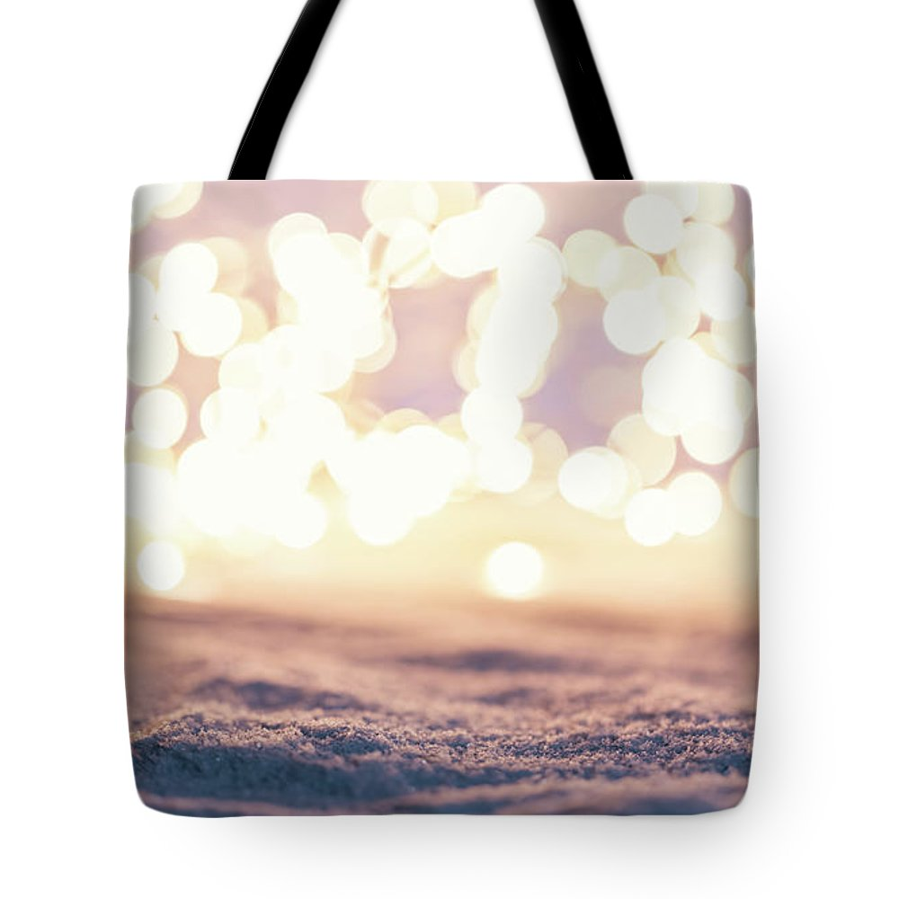 Winter Tote Bag featuring the photograph Winter Background With Snow And Fairy Lights. by Michal Bednarek