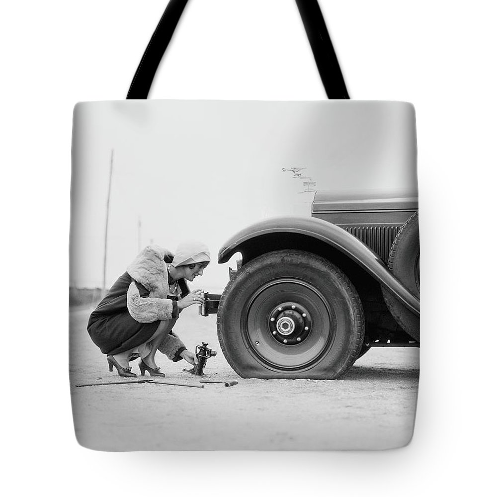 People Tote Bag featuring the photograph Woman Changing Flat Tire On Car by H. Armstrong Roberts