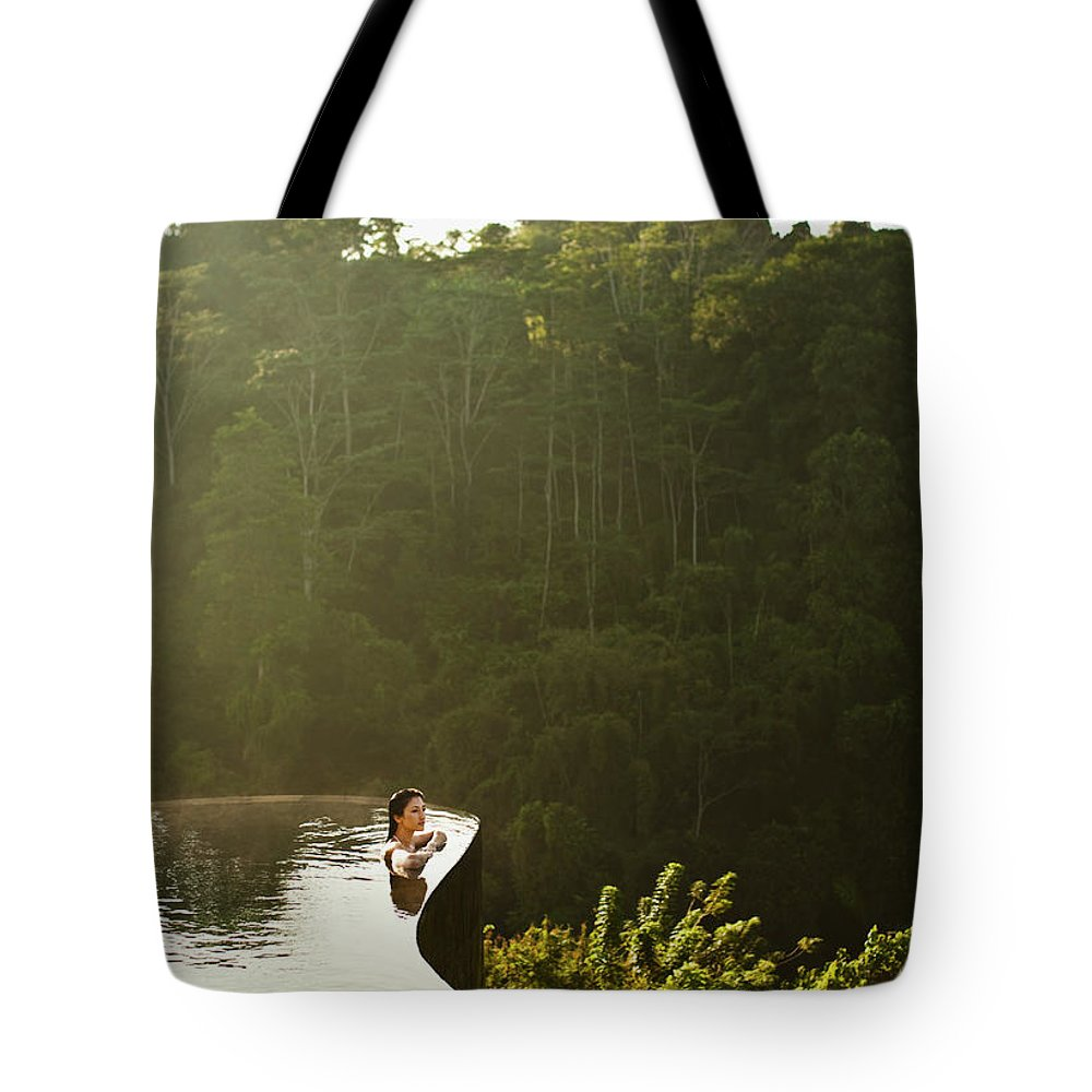 Tropical Rainforest Tote Bag featuring the photograph Woman In Infinity Pool At Sunrise. Bali by Matthew Wakem