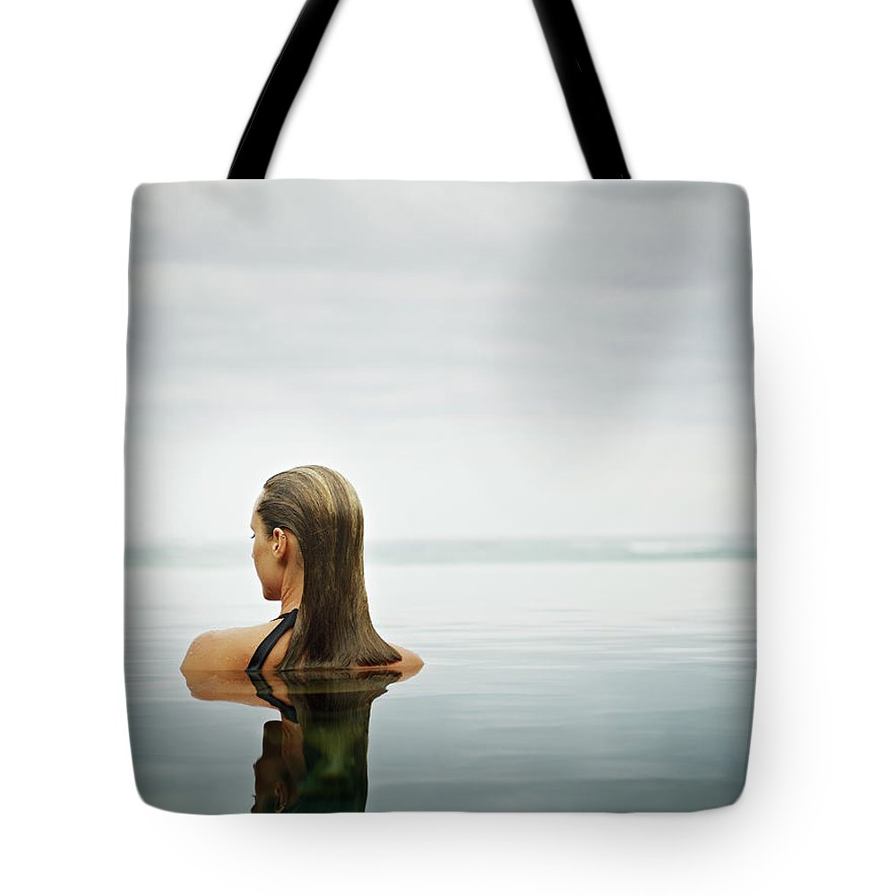 People Tote Bag featuring the photograph Woman Standing In Infinity Pool by Thomas Barwick