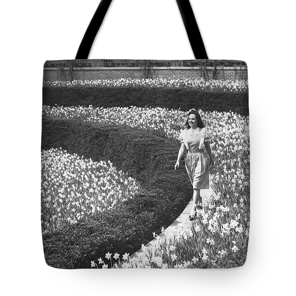 Flowerbed Tote Bag featuring the photograph Woman Walking On Flowerbed, B&w by George Marks
