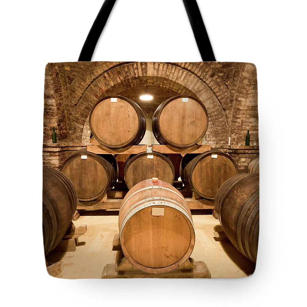 Arch Tote Bag featuring the photograph Wooden Barrels In Wine Cellar by Benedek