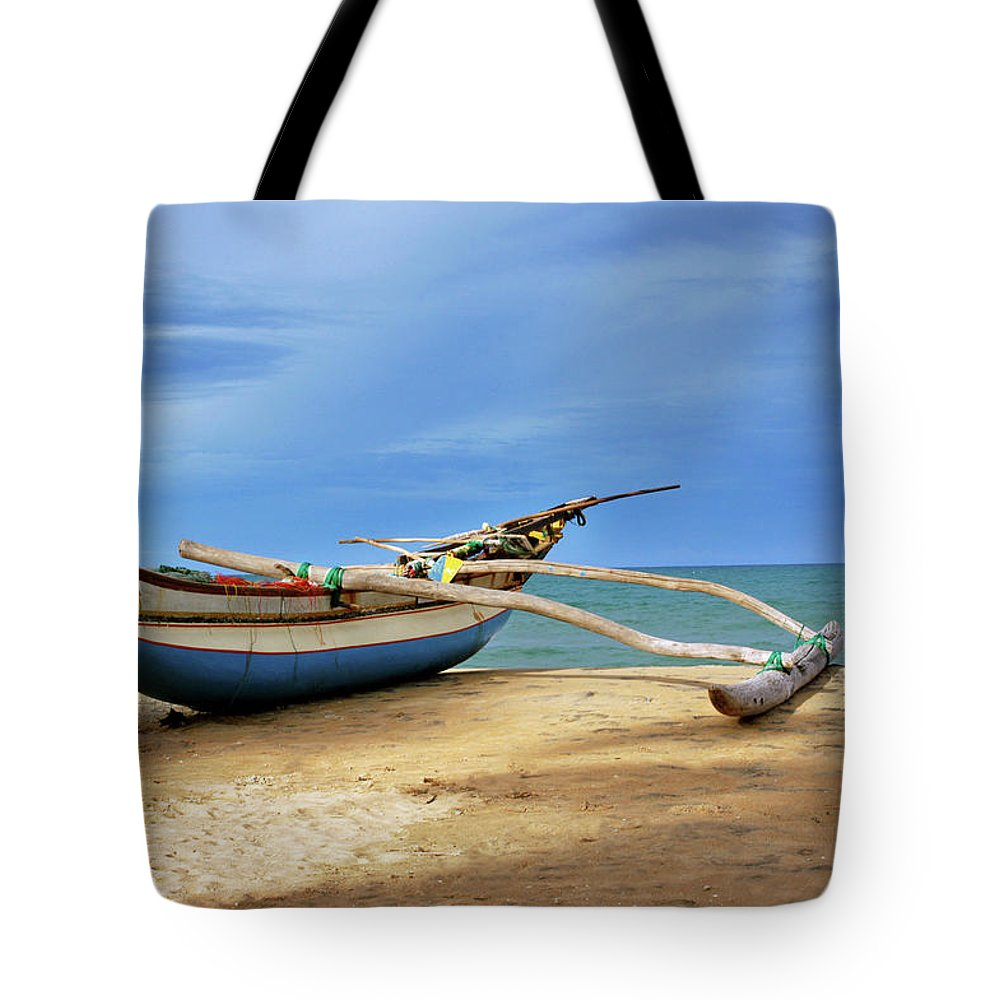 Tranquility Tote Bag featuring the photograph Wooden Catamaran By The Sea Shore by Juavenita Alphonsus