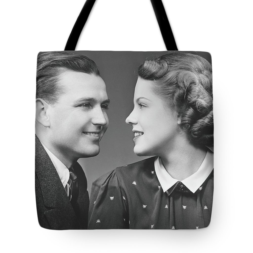 Young Men Tote Bag featuring the photograph Young Couple Looking In Eyes In Studio by George Marks