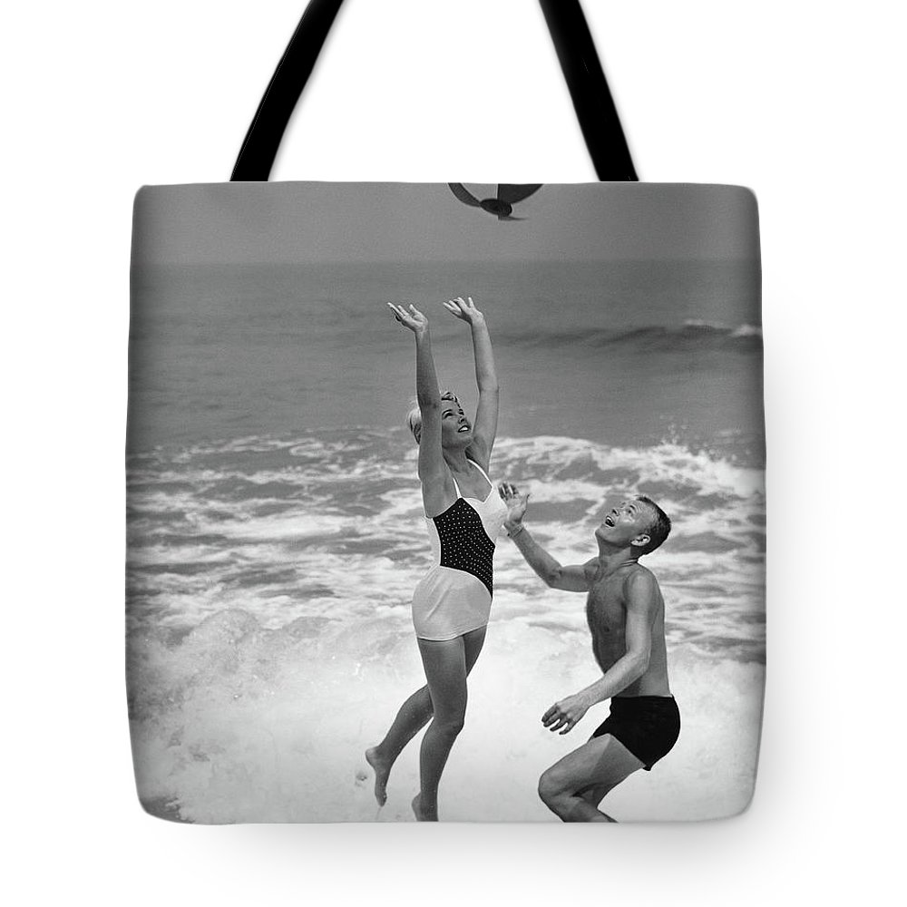 Young Men Tote Bag featuring the photograph Young Couple Playing With Beach Ball At by Stockbyte