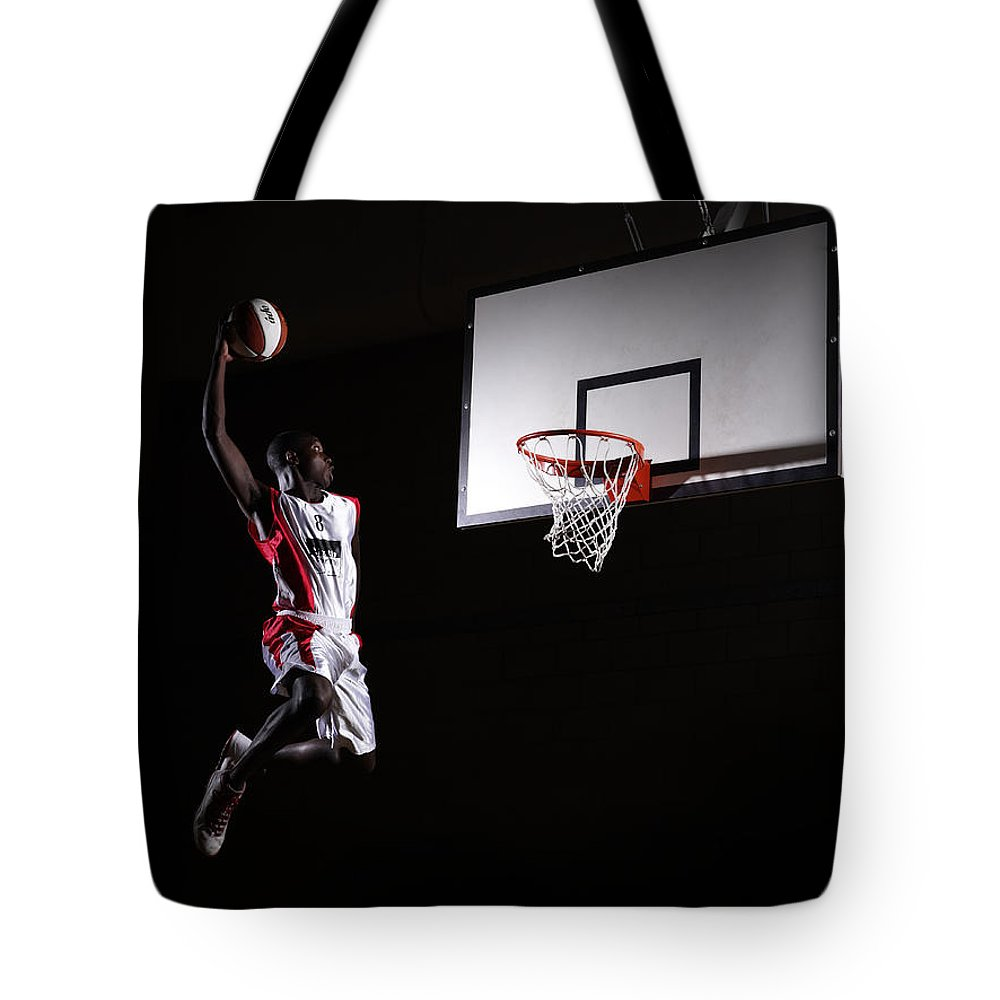 Human Arm Tote Bag featuring the photograph Young Man In The Air About To Dunk The by Compassionate Eye Foundation/steve Coleman/ojo Images Ltd