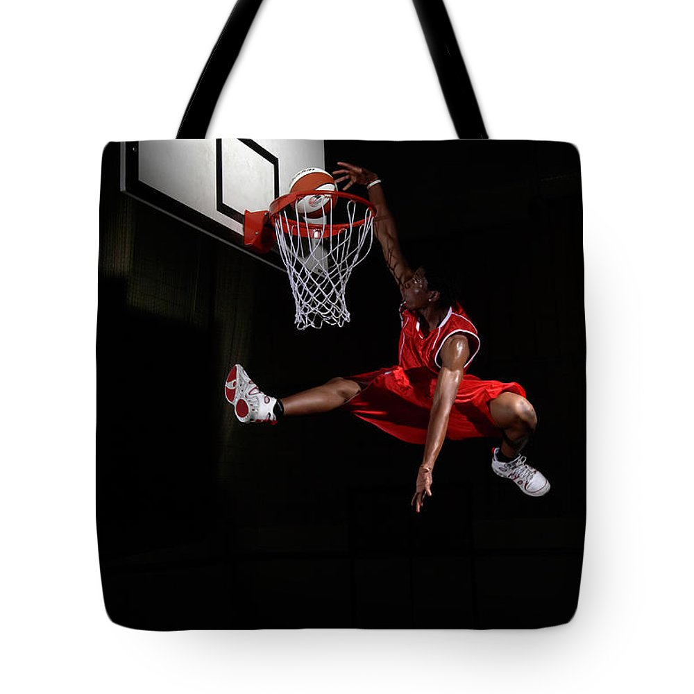 Human Arm Tote Bag featuring the photograph Young Man Making A Fancy Dunk by Compassionate Eye Foundation/steve Coleman/ojo Images Ltd