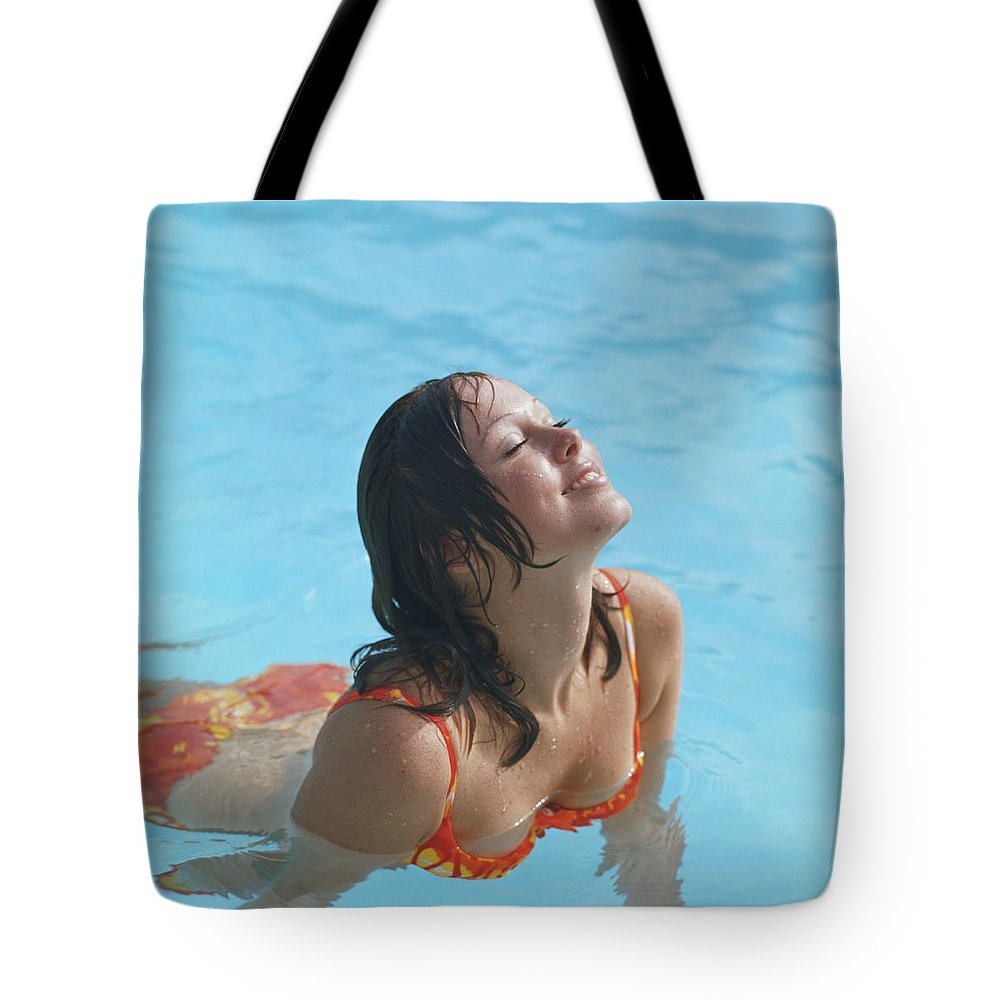 1973 Tote Bag featuring the photograph Young Woman In Bikini At Swimming Pool by Tom Kelley Archive