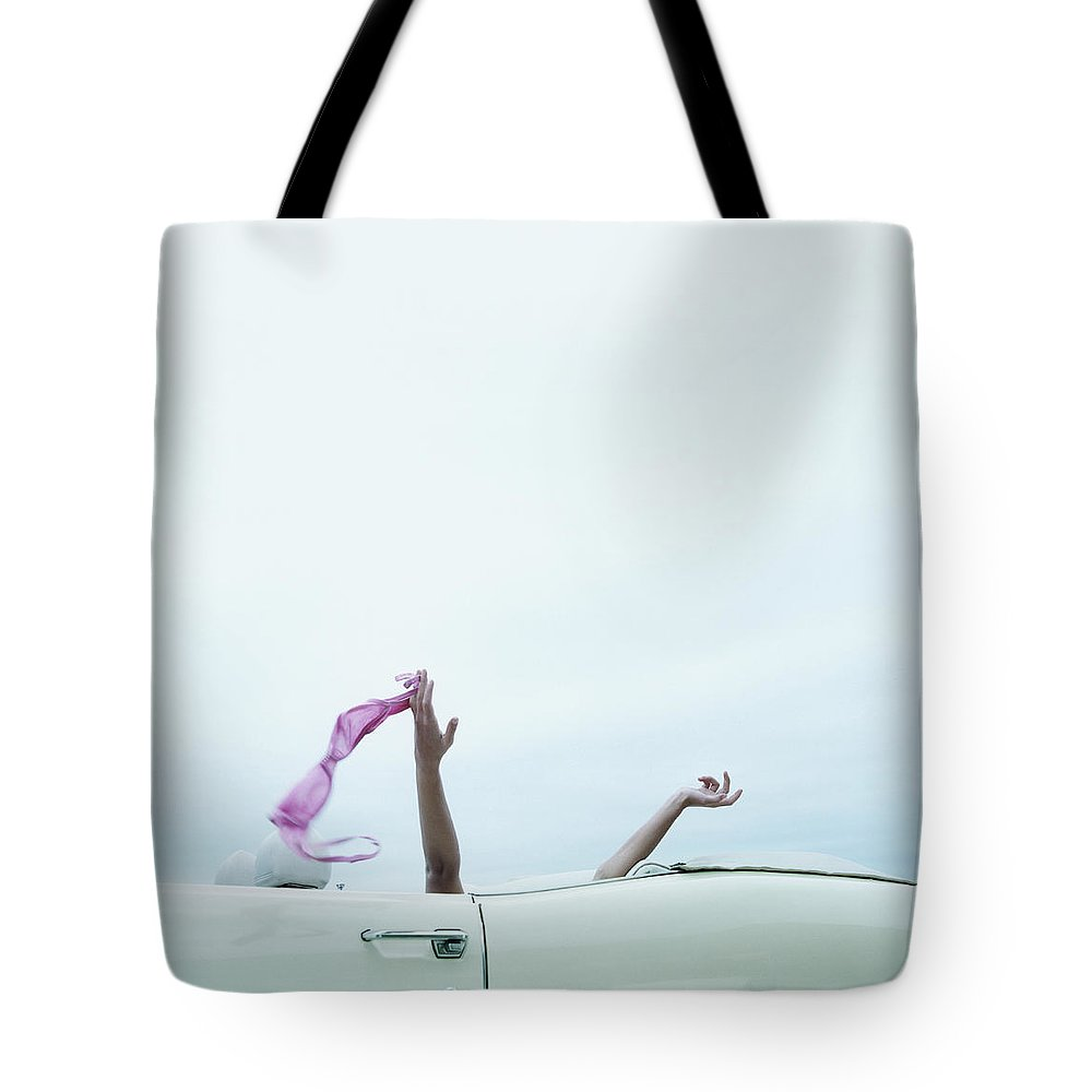 Young Men Tote Bag featuring the photograph Young Woman In Convertible Car, Arms by Jerome Tisne