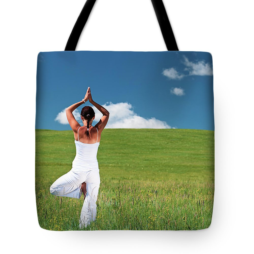 Scenics Tote Bag featuring the photograph Young Woman Practicing Yoga by Hadynyah
