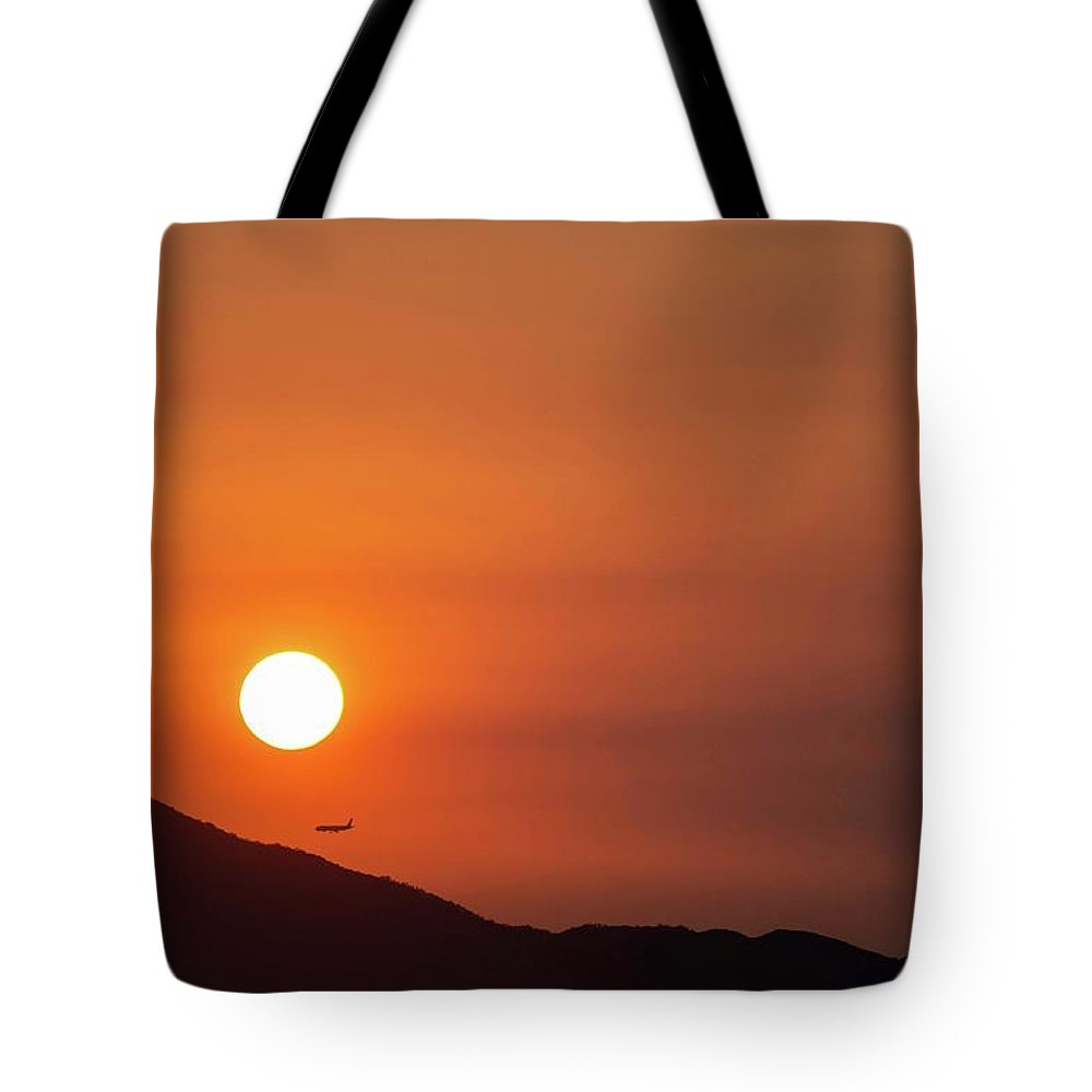 Sunset Tote Bag featuring the photograph Red sunset and plane in flight by Hannes Roeckel