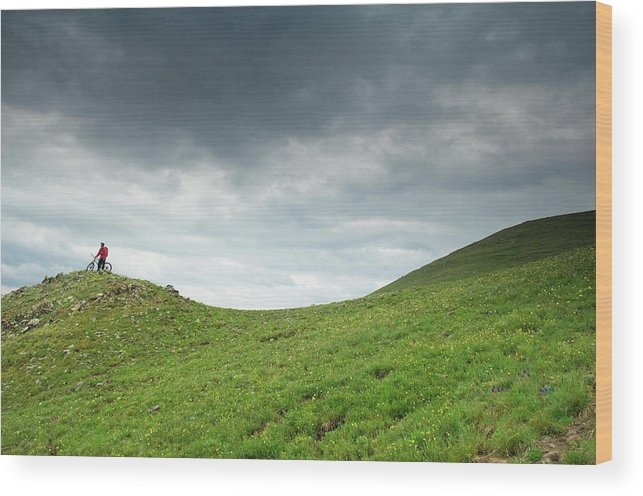 Bicycle Wood Print featuring the photograph A Man Sitting On Top Of A Tundra Ridge by Keith Ladzinski