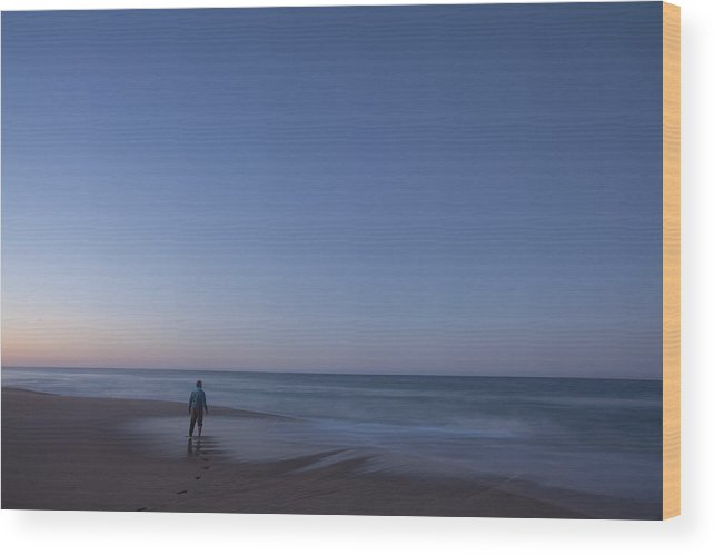Ocean Wood Print featuring the photograph A Man Standing On A Beach As Waves Roll by Woods Wheatcroft