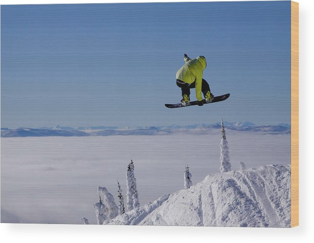Adventure Wood Print featuring the photograph A Snowboarder Catches Air Off A Jump by Noah Couser