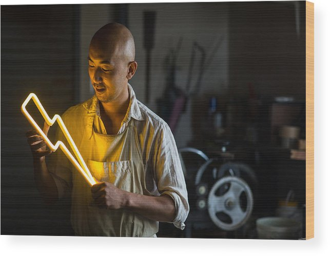 Working Wood Print featuring the photograph Craftsmen Holding A Lightning Bolt Shaped Neon Light by Trevor Williams