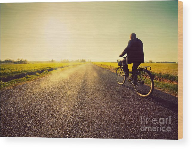 Road Wood Print featuring the photograph Old Man Riding A Bike To Sunny Sunset Sky by Michal Bednarek