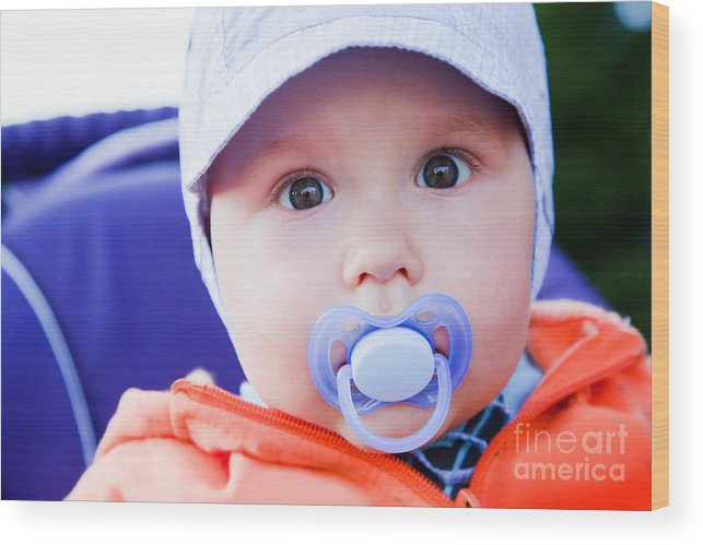 Child Wood Print featuring the photograph Young Baby Boy With A Dummy In His Mouth Outdoors by Michal Bednarek
