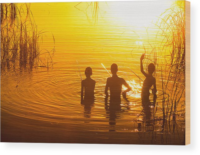 Fishing Wood Print featuring the photograph Three Young Kids Fishing On The Lake At Sunset by Matusciac Alexandru