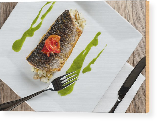 Grey Mullet Wood Print featuring the photograph Grey Mullet With Watercress Sauce Presented On A Square White Plate With Cutlery And Napkin by Andy Smy