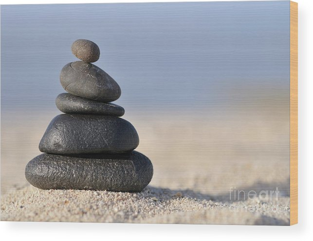 Order Wood Print featuring the photograph Stack Of Black Pebbles On Beach by Sami Sarkis