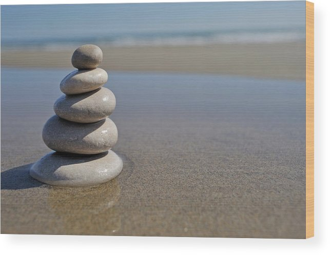 Stability Wood Print featuring the photograph Stack Of Pebbles On Beach by Sami Sarkis