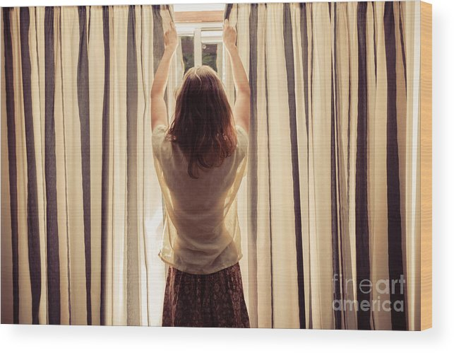 Woman Wood Print featuring the photograph A Young Woman Is Opening The Curtains by Lolostock