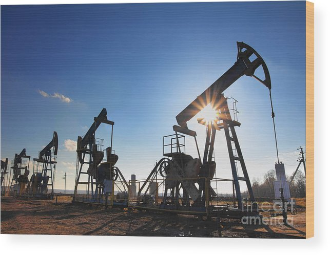 Steel Wood Print featuring the photograph Working Oil Pumps Silhouette Against Sun by Kokhanchikov