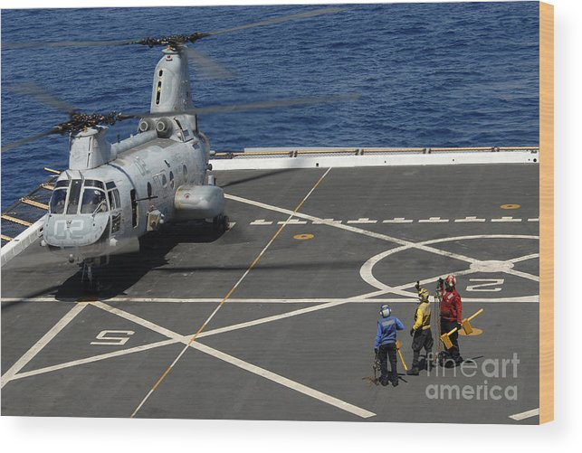 Military Wood Print featuring the photograph A Plane Captain Signals To A Ch-46e Sea by Stocktrek Images