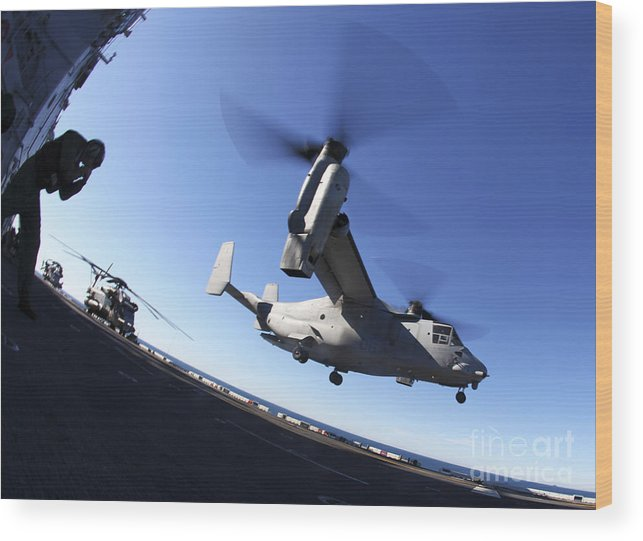 Warship Wood Print featuring the photograph An Mv-22 Osprey Lands Aboard The Uss by Stocktrek Images