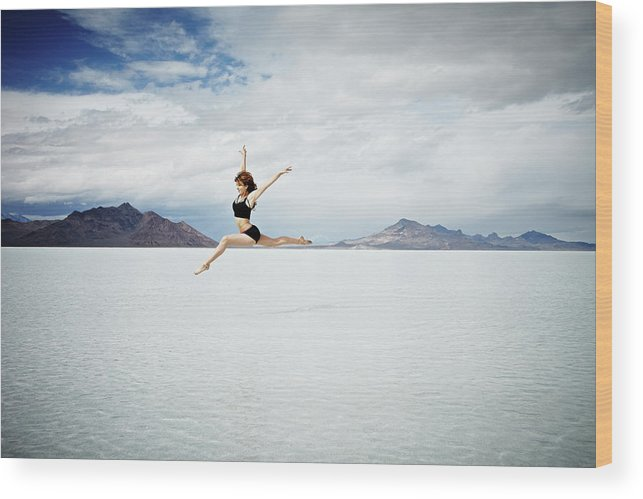 Ballet Dancer Wood Print featuring the photograph Ballerina Leaping In Mid-air Over Lake by Thomas Barwick