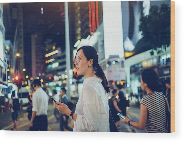 Financial Building Wood Print featuring the photograph Beautiful Asian woman using mobile phone while crossing road in busy downtown city street at night by D3sign