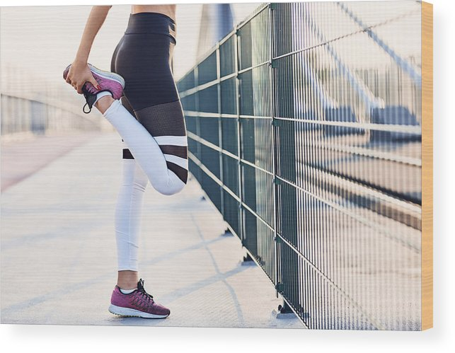 Recreational Pursuit Wood Print featuring the photograph Close-up of woman stretching legs after running by Westend61