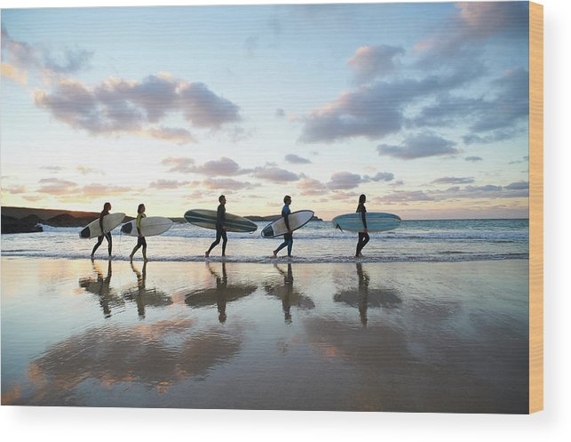 Young Men Wood Print featuring the photograph Five Surfers Walk Along Beach With Surf by Dougal Waters