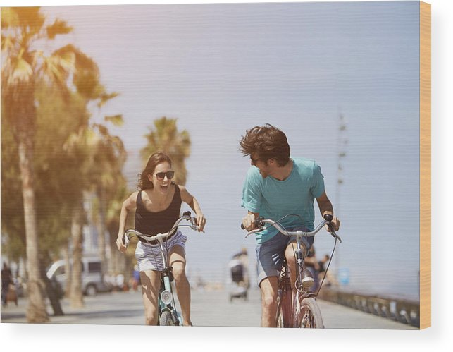Young Men Wood Print featuring the photograph Woman chasing man while riding bicycle by Morsa Images