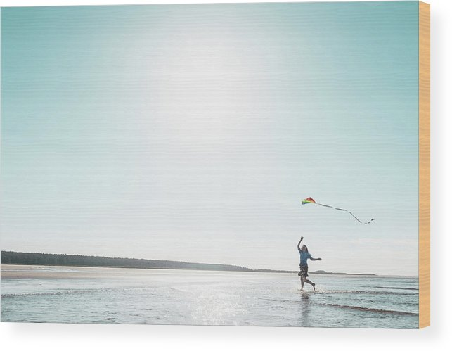 Three Quarter Length Wood Print featuring the photograph Woman Flying Kite On Beach by Dan Brownsword