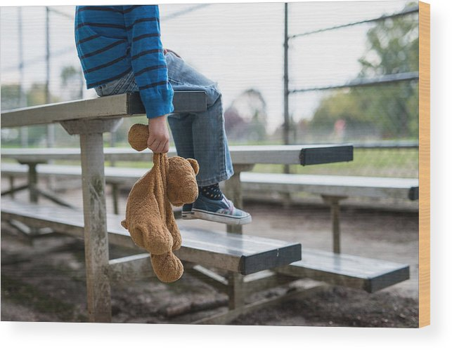 Empty Wood Print featuring the photograph Young boy sitting by himself on on bleachers. by FatCamera