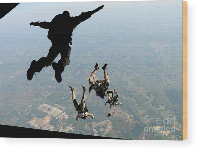 People Wood Print featuring the photograph Navy Seals Jump From The Ramp Of A C-17 by Stocktrek Images