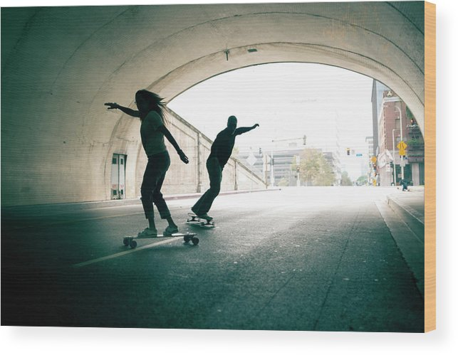 Mature Adult Wood Print featuring the photograph Couple Skateboarding Through Tunnel by Ian Logan
