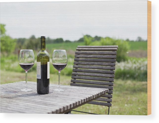 Five Objects Wood Print featuring the photograph Glasses And A Bottle Of Red Wine On An by Halfdark