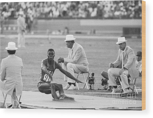 1980-1989 Wood Print featuring the photograph Lewis In The Long Jump At Olympics by Bettmann
