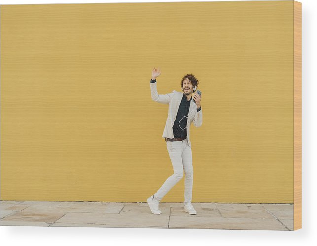 Hand Raised Wood Print featuring the photograph Businessman singing and dancing in front of yellow wall listening music with headphones and smartphone by Westend61