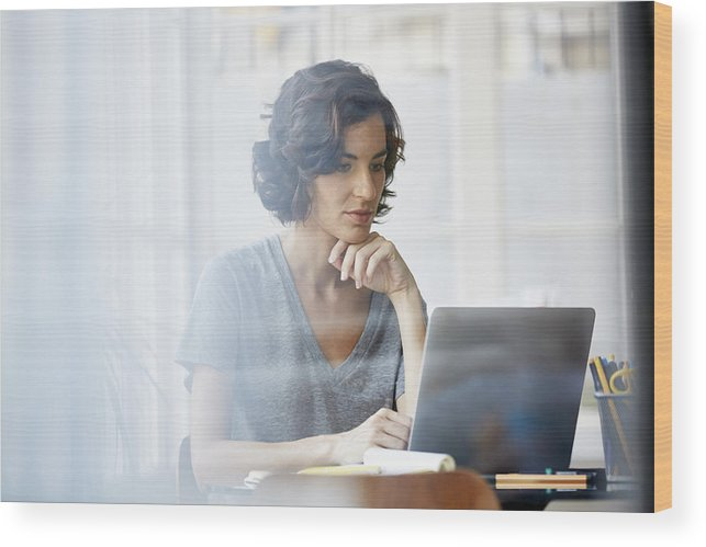 Working Wood Print featuring the photograph Businesswoman using laptop in office by Morsa Images
