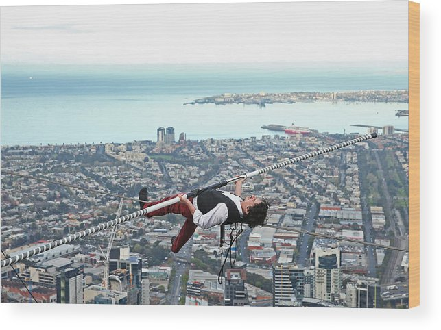 Artist Wood Print featuring the photograph High-wire Artist Kane Petersen Performs Tightrope Walk Over Melbourne CBD by Scott Barbour